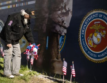 Veteran Patrick Watson places a wreath at the base of a new Mural Arts Philadelphia piece titled