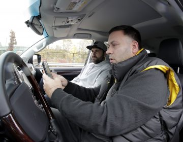 In a photo taken Friday, Nov. 9, 2018, in Bayonne, N.J., Lenny Sciascia, (right), and his friend Mario DeAngelis look at betting lines for the day's sporting events before placing bets in a parking lot just off the Bayonne Bridge, which divides New York and New Jersey. Sciascia, who lives in Staten Island, N.Y., commutes regularly to places his bets from New Jersey, where online betting is legal. With sports betting being advertised all around them but the opportunity to actually do it restricted to just one nearby state, gamblers from New York and Pennsylvania are crossing bridges and tunnels into New Jersey to make legal sports bets. (Julio Cortez/AP Photo)