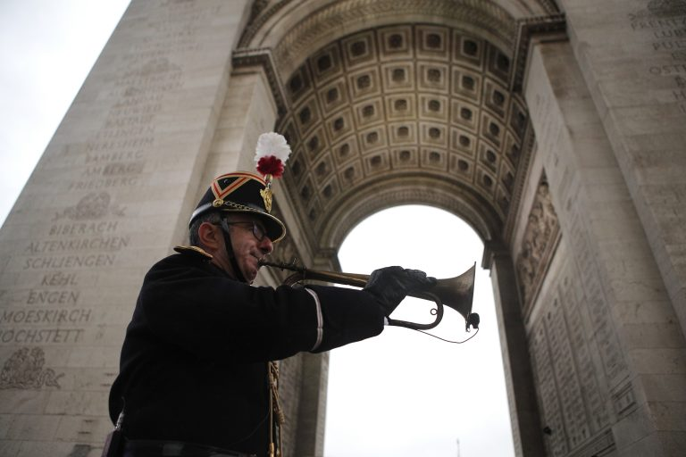 Military officer Garcia plays the original Armistice bugle from 1918 under the Arc de Triomphe Sunday, Nov. 11, 2018 in Paris. More than 60 heads of state and government are in France for the Armistice ceremonies at the Tomb of the Unknown Soldier in Paris on the 11th hour of the 11th day of the 11th month, exactly a century after the armistice. (AP Photo/Francois Mori, Pool)