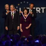 Former U.S. Vice President Joe Biden, from left, bestows a medal on former U.S. President George Bush as former First Lady Laura Bush has the same bestowed by Doug DeVos, Executive Committee Chairman for the National Constitution Center, at the National Constitution Center Sunday, Nov. 11, 2018 in Philadelphia. Both received the 30th Annual Liberty Medal, an honor given to those who are committed to freedom and human rights globally. (AP Photo/Corey Perrine)