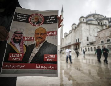 A man holds a poster showing images of Saudi Crown Prince Muhammed bin Salman and of journalist writer Jamal Khashoggi, describing the prince as