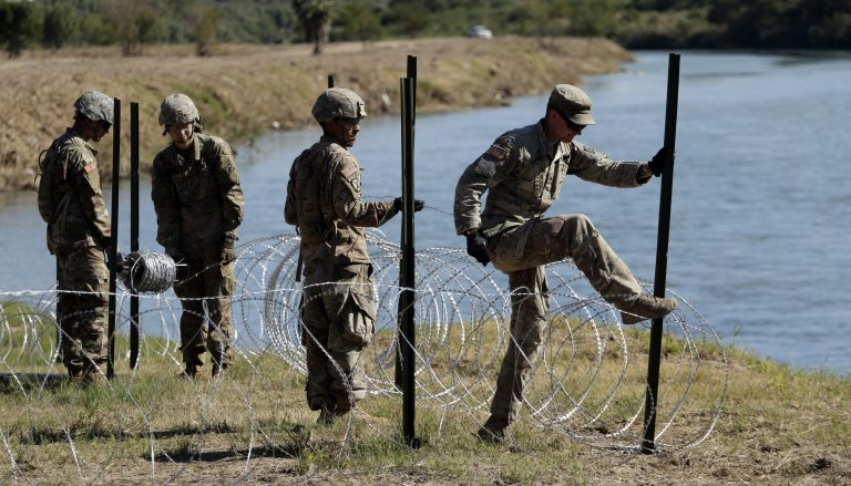 Members of the U.S. military install multiple tiers of concertina wire along the banks of the Rio Grande near the Juarez-Lincoln Bridge at the U.S.-Mexico border, Friday, Nov. 16, 2018, in Laredo, Texas. (AP Photo/Eric Gay)