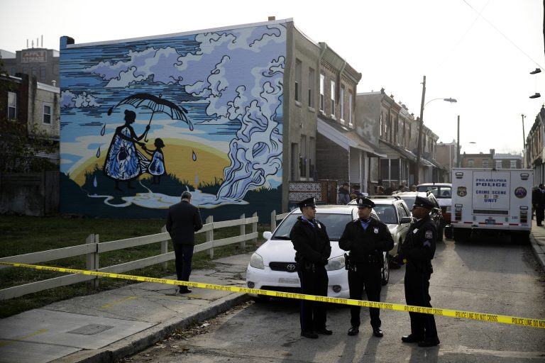 Police gather at the scene of a fatal shooting in the center row home in Philadelphia, Monday, Nov. 19, 2018. Police say two men and two women have been found shot and killed in a basement in Philadelphia. (AP Photo/Matt Rourke)