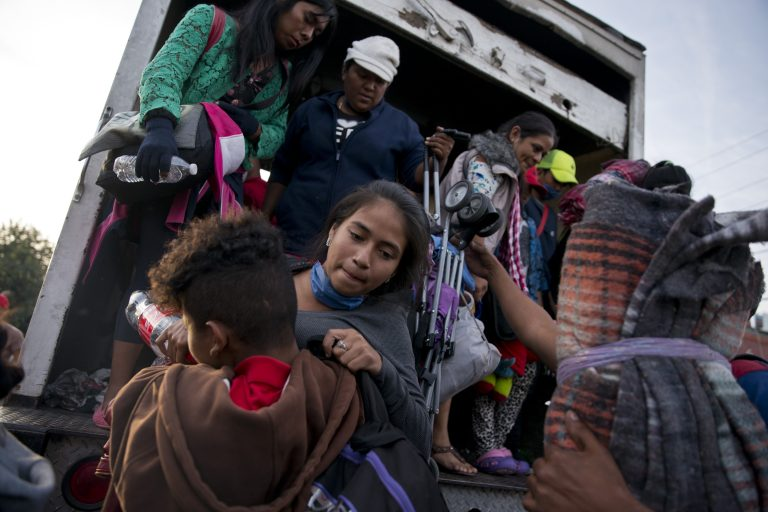 Migrants arrive to Tijuana after traveling in a truck from Mexicali, part of the migrant caravan, in Mexico, Tuesday, Nov. 27, 2018. Tension continued Tuesday as residents in the Mexican border city of Tijuana closed down a school next to a sports complex where more than 5,000 Central American migrants have been camped out for two weeks. (Ramon Espinosa/AP Photo)
