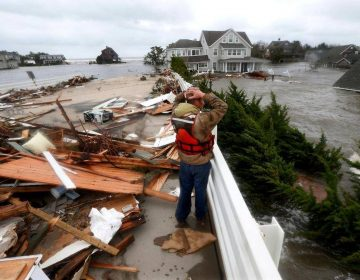 Brian Hajeski, 41, of Brick, N.J., reacts as he looks at debris of a home that washed up on to the Mantoloking Bridge the morning after superstorm Sandy rolled through in Mantoloking, N.J., Oct. 30, 2012. JULIO CORTEZ/AP