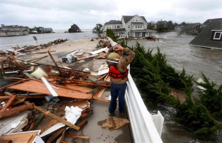 Brian Hajeski, 41, of Brick, N.J., reacts as he looks at debris of a home that washed up on to the Mantoloking Bridge the morning after superstorm Sandy rolled through in Mantoloking, N.J., Oct. 30, 2012. (Julio Cortez/AP Photo)