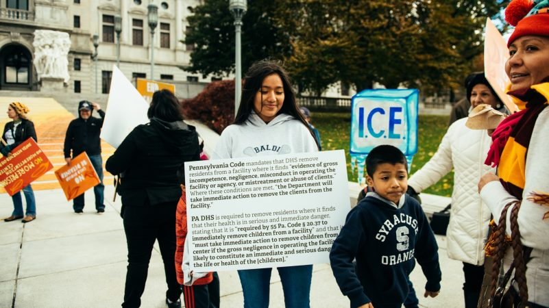 Adamaris Lopez of Philadelphia holds a sign with text excerpts of legal arguments from the Sheller Center for Social Justice of the Temple University Beasley School of Law. She joined a protest outside the Pennsylvania Capitol organized around the work of muralist Michelle Angela Ortiz. (Dani Fresh fpr WHYY)