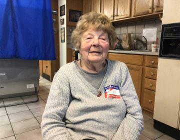 "Louise deVirgillo is 98-years-old and helping people with the voting machines. She's been working at Brookhaven's 2nd Precinct every election for 40 years. She says she's ""never seen people so excited for a midterm."" (Robert Brod/WHYY)"