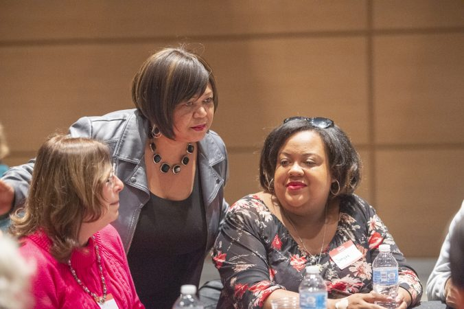 Sandra Clark talks with community members prior to the beginning of table discussions. (Jonathan Wilson for WHYY)