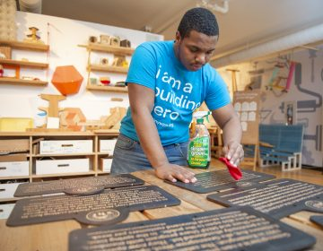 Najaye Davis cleans signs after they are cut by a laser cutter. (Jonathan Wilson for WHYY)