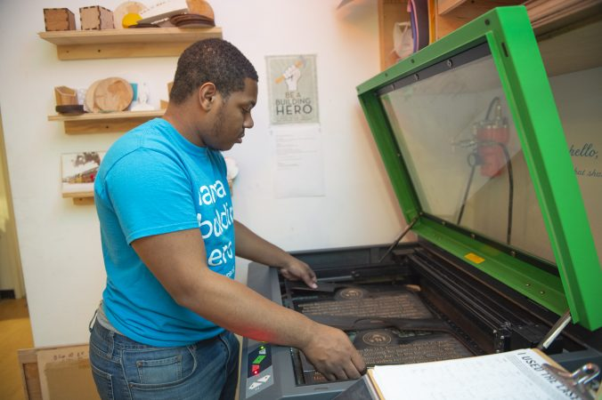 Najaye Davis removes signs from a laser cutter after they have been etched and trimed. (Jonathan Wilson for WHYY)