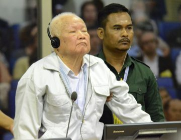 Khieu Samphan, (left), former Khmer Rouge head of state, stands at the dock in a court room during a hearing at the U.N.-backed war crimes tribunal in Phnom Penh, Cambodia, on Friday. (Nhet Sok/AP/Extraordinary Chambers in the Courts of Cambodia)