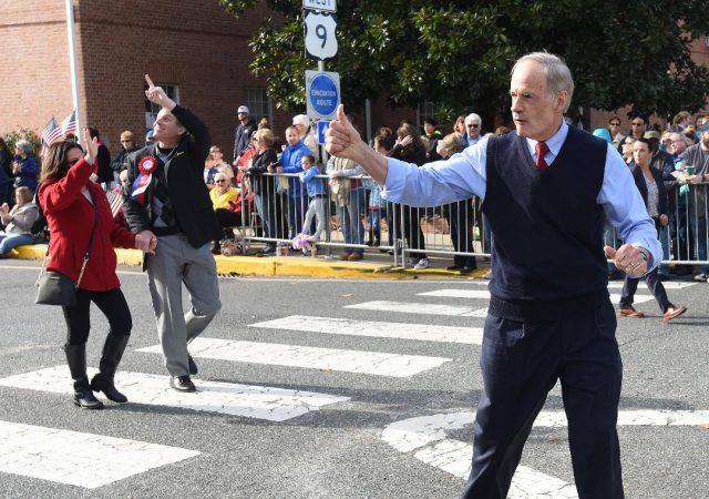 U.S. Sen. Tom Carper (right) waves to the crowd as his Republican opponent Rob Arlett walks along the parade route. Carper beat Arlett to win a fourth term in the U.S. Senate. (Chuck Snyder/for WHYY)