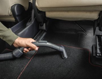 A man cleans the carpet in his car with vacuum cleaner. (Bigstock Image)
