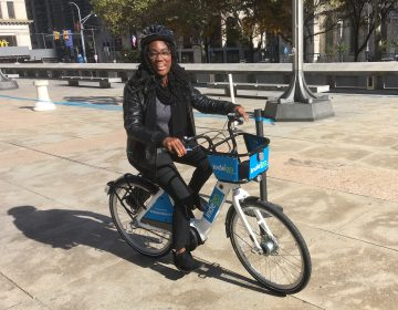 Chamarra McCrorie gives Indego's new e-bikes a test ride on Thomas Paine Plaza. (Jim Saksa/WHYY)
