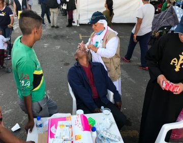 Sister Bertha Lopez Chaves applies anti-inflammatory eyedrops to a migrant at a stadium in Mexico City where the caravan is resting. Her order is one of roughly 50 groups giving aid to the migrants in the Mexican capital.