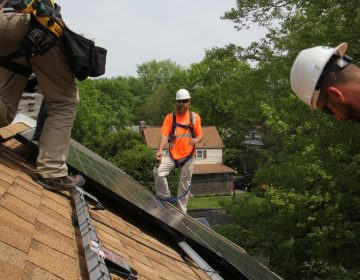 Dennis Hajnik (center) directs a solar panel installation in Bryn Mawr. (Emma Lee/WHYY)