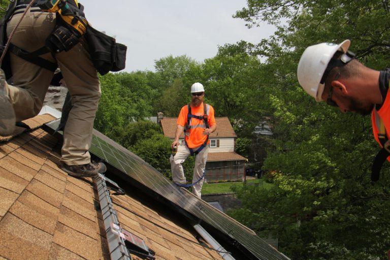 Dennis Hajnik (center) directs a solar panel installation in Bryn Mawr. (Emma Lee/WHYY)