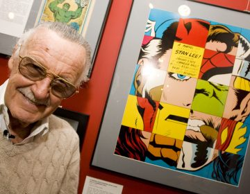 Comic book legend Stan Lee poses at the opening reception for