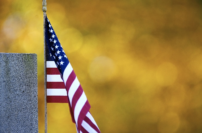 An American flag blows in the wind surrounded by the color of autumn leaves at Antietam National Cemetery in Sharpsburg, Md., Thursday, November 8, 2018. November 11, 2018 is Veterans Day and marks 100 years since the end of World War I.  (Colleen McGrath/The Herald-Mail via AP)