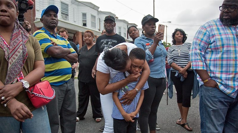 Sakinah Crew comforts her 7-year-old son, Swyhir, during a rally to seek justice for the death of Sandrea Williams. She was killed in a random act of gun violence outside of her mother's home in West Philadelphia. Their teenage cousin was also injured by gunfire that night. (Emily Cohen for WHYY)
