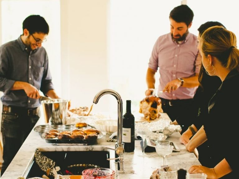 Michael Durand (left), husband of Kitchn Editor-In-Chief Faith Durand, and friend Chris Gardner (right) carve turkey while guests hang out in the Durands' kitchen at a recent party, dirty dishes and all. (Kitchn/Rachel Joy Barehl)