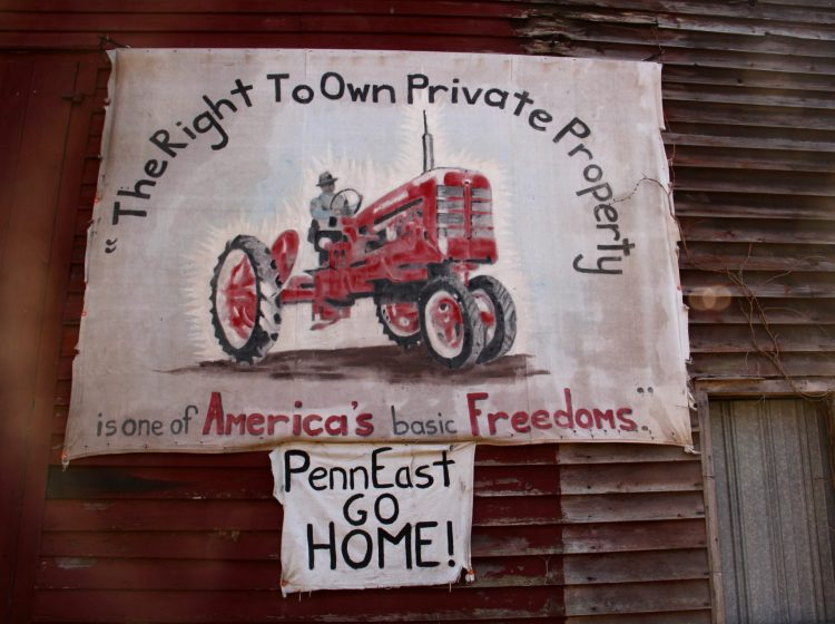 A sign on the side of a barn on Riegelsville Road in Holland Township, New Jersey, shows local opposition to the PennEast pipeline. (Emma Lee/WHYY)