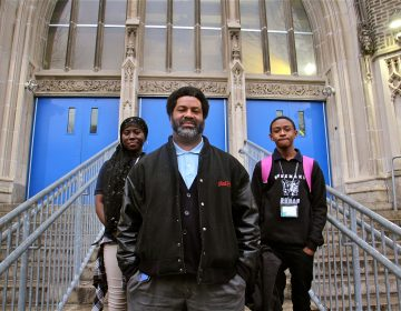 Sharif El-Mekki, principal of Mastery Shoemaker Elementary in Philadelphia, founded a group that seeks to boost the number of black male educators. Here he stands at the entrance to the school with students Essi Gasonu (left) and Bryce Thompson.
