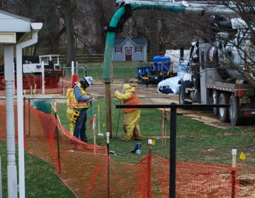 In this photo from May 2018, pipeline workers probe the ground on Lisa Drive in West Whiteland Township where sinkholes have developed as a result of the Mariner East 2 construction. (Jon Hurdle/StateImpact Pennsylvania)
