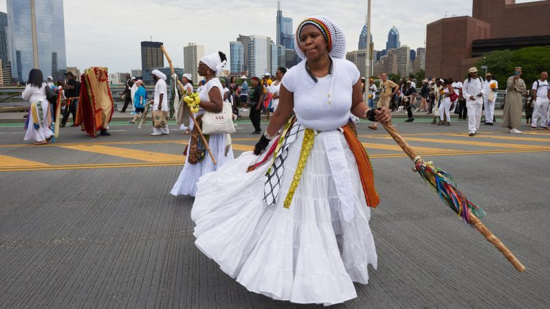 Yannie dances over the South Street Bridge before the procession to Oshun, the Goddess of the River, during the Odunde festival on June 10, 2018. (Natalie Piserchio for WHYY)