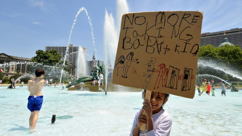 Olivia, 5, daughter of an undocumented immigrant father from Mexico, stands in the fountain holding a self-made sign. She's joined by her family as they take part in the End Family Deportation rally, on June 30, 2018. (Bastiaan Slabbers for WHYY)