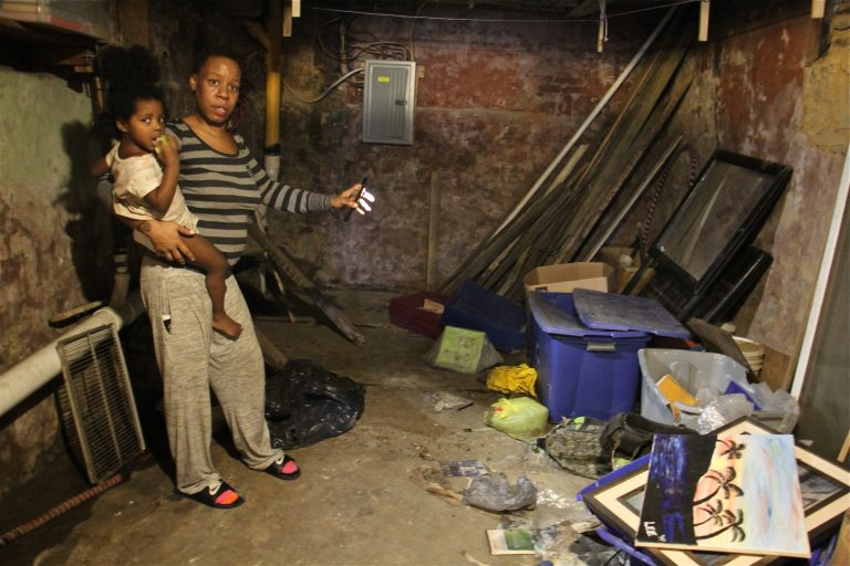 Sherri Lee, holding her 2-year-old daughter, Aubrey Boyd, shines a light on possessions that were destroyed when a backed up toilet flooded her basement. (Emma Lee/WHYY)