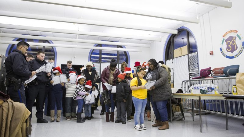 About ten Philadelphia police officers and twenty members of the Hunting Park community gather at the 39th Police District to sing Christmas carols on December 7. Crystal Cooper (right) and her granddaughter, Promise Cooper (second from right), attended the event so that the police officers could have the opportunity to