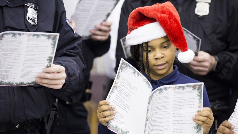 Jacqueline Tyler, 8, a ballet student at the Georgia E. Gregory Interdenominational School Of Music, sings Christmas carols alongside officers at the 39th Police District on December 7. Tyler and her grandmother, Marian (not pictured), have been coming to the annual event for three years