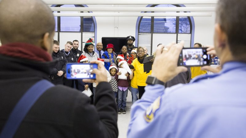Marcell Basett (left), public relations for the Police Advisory Commission, and Officer Joe Lukaitis, co-founder of the Caroling with a Cop event, take group photographs of the community members and police officers who showed up to sing Christmas carols together on December 7. (Rachel Wisniewski for WHYY)