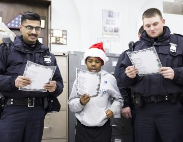 Officers Rana Ashfaq (left) and Joe Crouse flank Kofi Walker, 9, at the Caroling with a Cop event held in collaboration between the 39th Police District and the Georgia E. Gregory Interdenominational School Of Music on December 7.