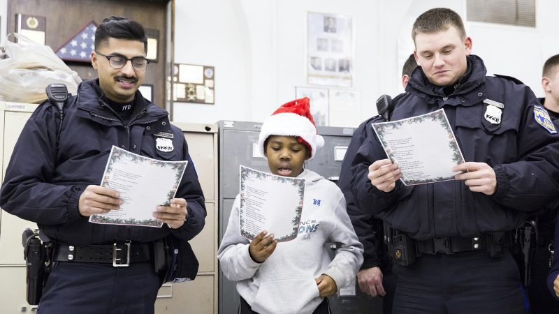 Officers Rana Ashfaq (left) and Joe Crouse flank Kofi Walker, 9, at the Caroling with a Cop event held in collaboration between the 39th Police District and the Georgia E. Gregory Interdenominational School Of Music on December 7. (Rachel Wisniewski for WHYY)