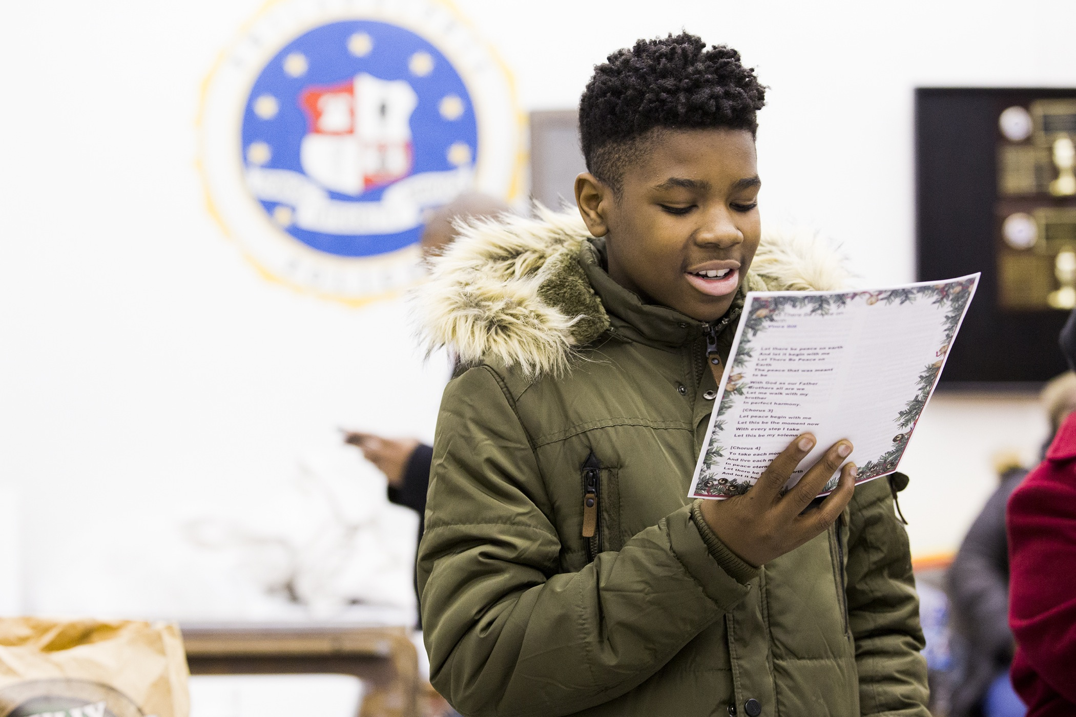 Despite being nervous to interact closely with police officers, Zion Nwalipenja, 13, reads a speech he composed in which he thanks the 39th Police District for attending the caroling event on December 7.