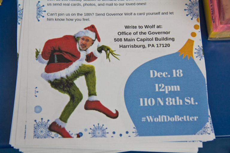A grinch Governor Wolf appears on a flyer inviting Philadelphians to create holiday cards to send to Governor Wolf asking him to end a DOC policy that doesn't allow families to send cards of photos to incarcerated family members. (Kimberly Paynter/WHYY)