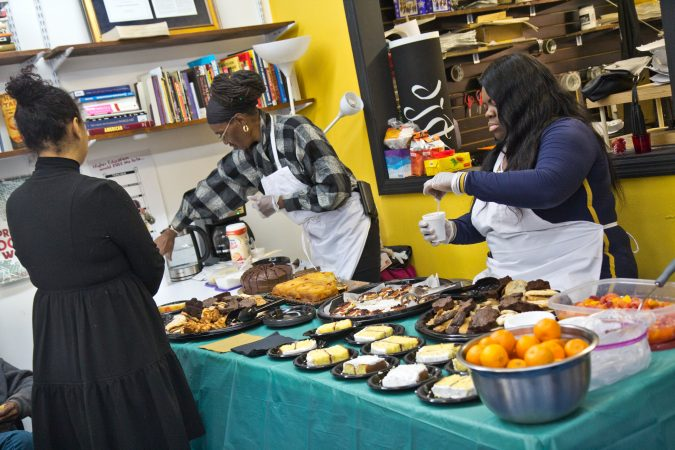 Fellows with the People's Paper Co-op serve treats at a community winter gathering. (Kimberly Paynter/WHYY)