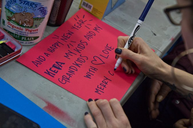 Community members make cards to send to incarcerated loved ones. (Kimberly Paynter/WHYY)