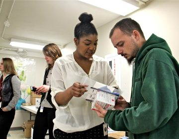 Charles Greif, 27, accepts a naloxone pack from Philadelphia health department worker Fatimah Maiga at Holmsburg Library, one of 80 sites across Pennsylvania where the overdose reversal drug was distributed for free.