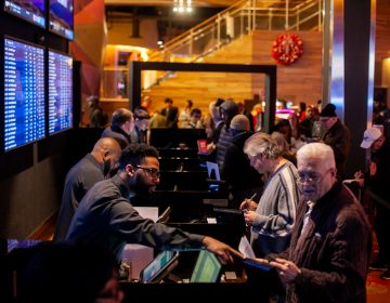 Prospective betters place their wagers on sports events at the SugarHouse Casino Saturday morning. (Brad Larrison for WHYY)
