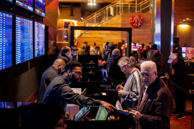 Prospective bettors place their wagers on sports events at the SugarHouse Casino Saturday morning. (Brad Larrison for WHYY)