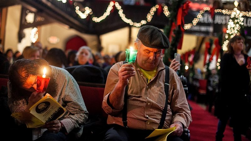 Bill Shriver (right) and Neil Davis, who is currently homeless, listen to the reading of 270 names of homeless or formerly homeless people who died in Philadelphia over the past year. (Brad Larrison for WHYY)