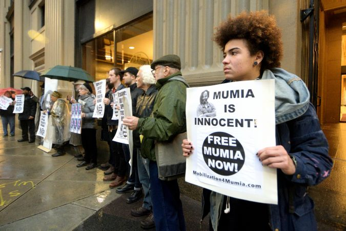 A group of two dozen activists briefly blocks traffic during a rally outside the Philadelphia district attorney's office on Friday. The group is urging District Attorney Larry Krasner to let stand  a Common Pleas Court ruling that allows Mumia Abu-Jamal to file an appeal. (Bastiaan Slabbers for WHYY)