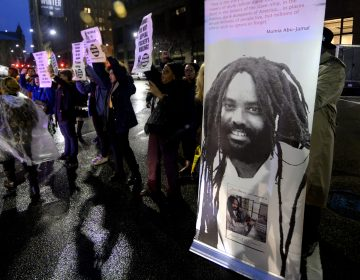 A group of two dozen activists briefly blocks traffic during a rally outside the Philadelphia district attorney's office in December. The group is urging District Attorney Larry Krasner not to challenge a Common Pleas Court ruling that allows Mumia Abu-Jamal to file an appeal of his murder conviction. (Bastiaan Slabbers for WHYY)