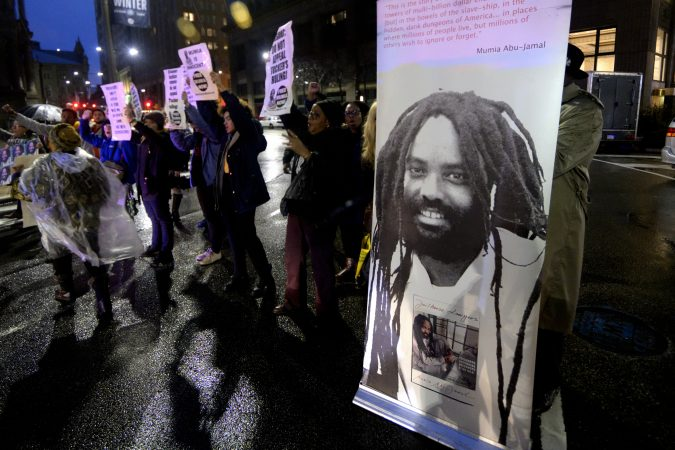 A group of two dozen activists briefly blocks traffic during a rally outside the Philadelphia district attorney's office Friday. The group is urging District Attorney Larry Krasner not to challenge a Common Pleas Court ruling that allows Mumia Abu-Jamal to file an appeal of his murder conviction. (Bastiaan Slabbers for WHYY)