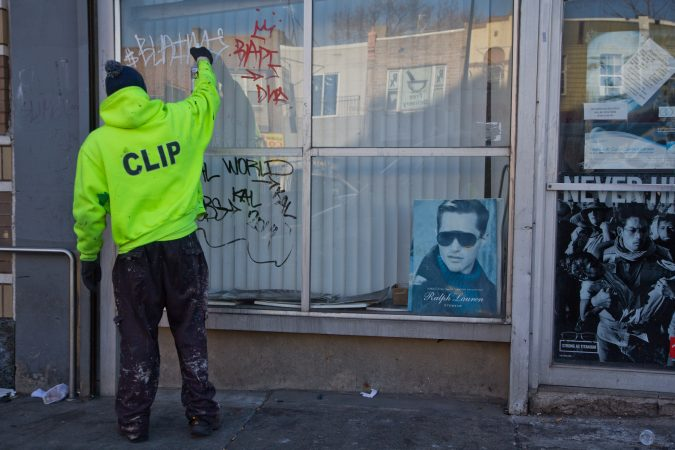 A clip worker removes graffiti around Kensington. (Kimberly Paynter/WHYY)