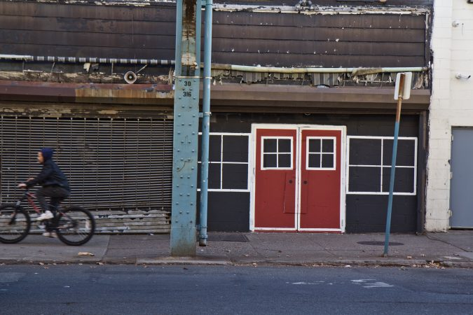 Boarded buildings are painted to have faux doors and windows in Kensington. (Kimberly Paynter/WHYY)